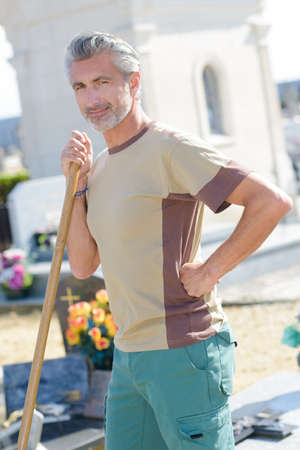 Portrait of man leaning on handle of tool