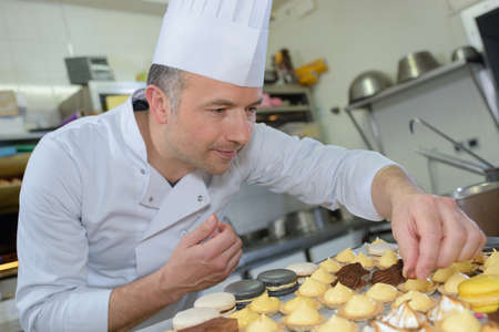 piped: Confectionner decorating cakes Stock Photo