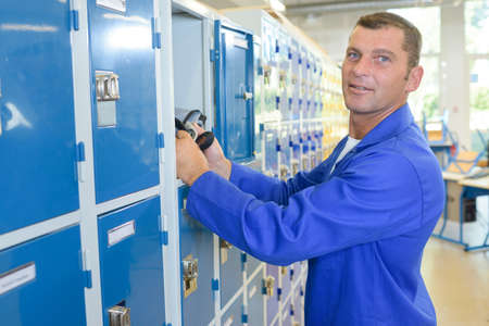 common room: Man putting belongings in a locker