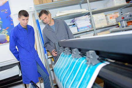 oversee: Two men overseeing profesisonal printing machine Stock Photo