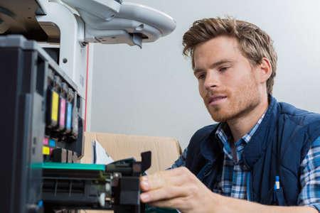 젊은 남성 기술자 사무실에서 프린터를 복구됩니다.