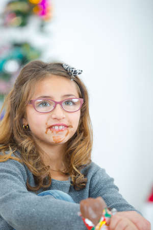 Girl eating chocolate, mouth in a mess Stock Photo