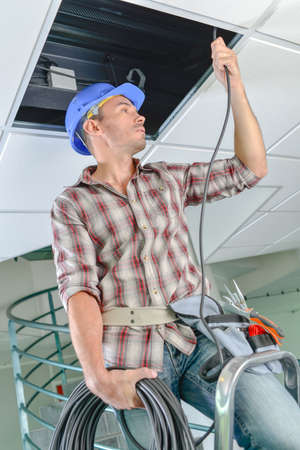 suspend: Man threading cable into space above suspended ceiling Stock Photo