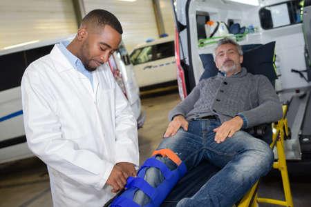 splint: Hombre en camilla, en la pierna férula Foto de archivo