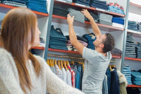 clothes rail: Man reaching jumper from shelf in clothes shop
