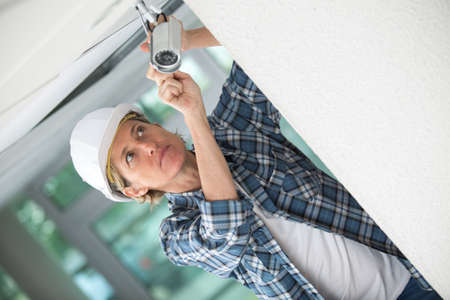 closed circuit television: Female contractor installing surveillance camera