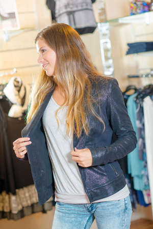Woman trying a jacket on in a shop Stock Photo