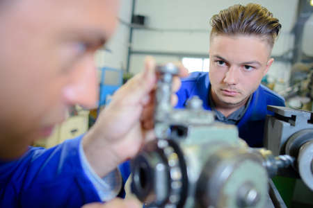 routing: engine assemblers working on a machine Stock Photo