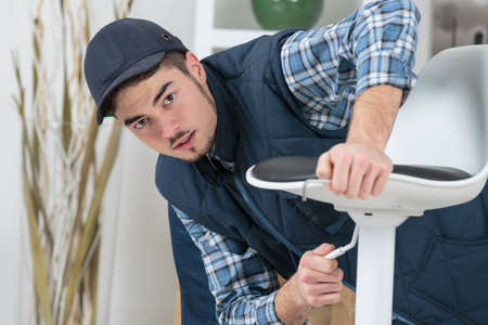 office tool: Man assembling chair Stock Photo