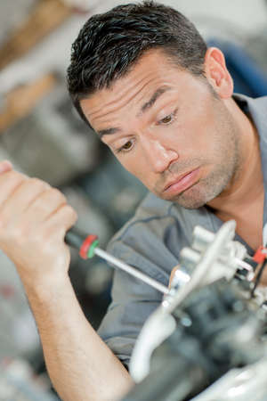 Mechanic using screwdriver, looking exhausted