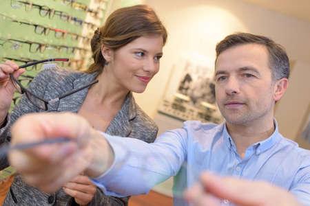 shortsighted: beautiful optician helping male customer choosing eye glasses