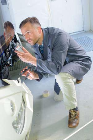 watertight: Mechanic using tube of sealant