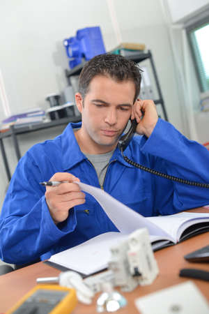 Man wearing overalls, on telephone Stock Photo