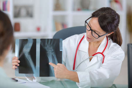 radiogram: female dentist showing x-rays to patient Stock Photo