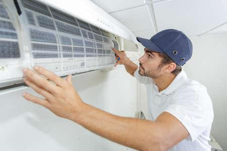 Retrato del técnico varón adulto de mediana edad reparación de aire acondicionado