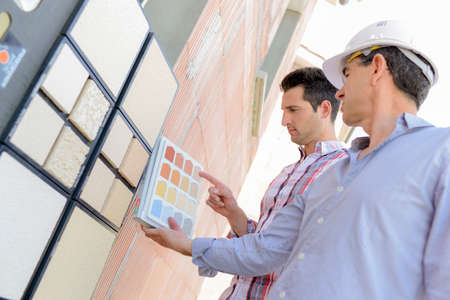 Two men matching colour samples on exterior wall