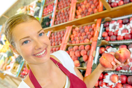 Shop assistant holding peaches Stock Photo