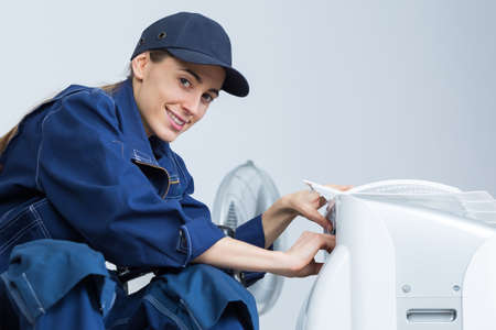 humidify: Woman working on air conditioning unit Stock Photo