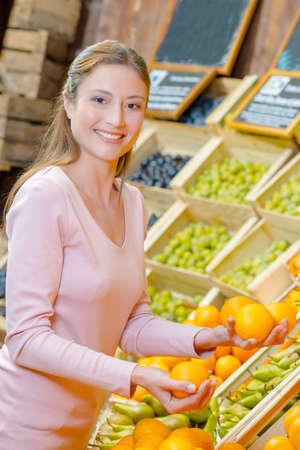 Lady choosing oranges in grocers