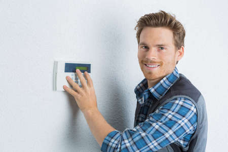 attractive young handyman checks the security alarm Stock Photo