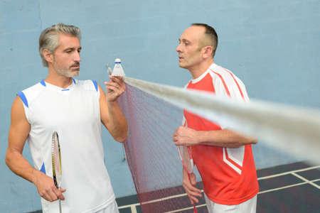 shuttlecock: badminton players holding a shuttlecock