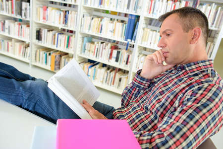 uncouth: Man reading in library with feet on table