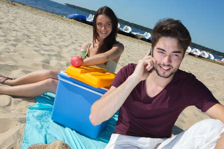 strapping: happy teenagers calling their friends while enjoying the beach