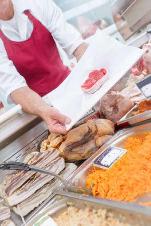 congenial: Butcher presenting cut of beef