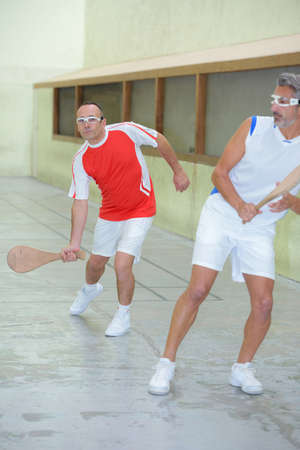 competitive sport: Men playing sport with wooden racket