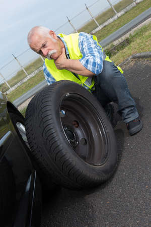 cabizbajo: discouraged retired man unable to change car tyre Foto de archivo