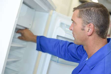 white goods: Repairman working on refridgerator