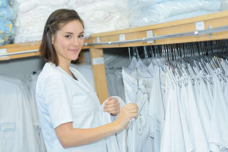 Woman next to rack of laundered uniforms