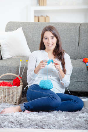 a hobby: Lady sat on floor knitting