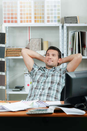 take a breather: Man sat at desk, leaning back hands behind his head