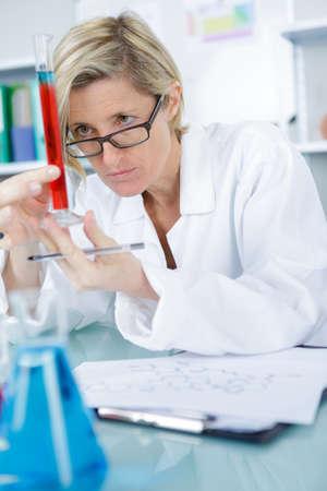 ah1n1: lady doctor looking at liquid in tube