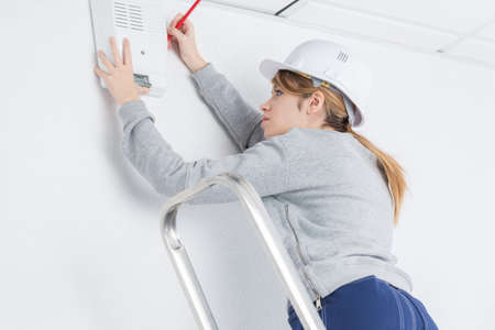 skilled labour: Woman fitting electrical appliance to wall