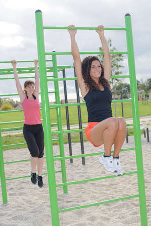 suspend: Women hanging from climbing frame in park