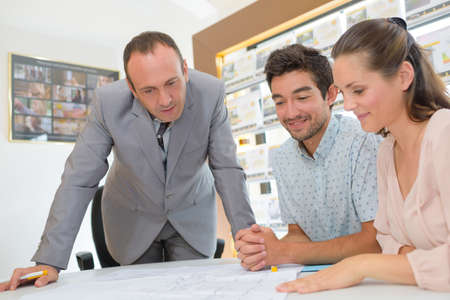 home working: Estate agent looking at plans with young couple Stock Photo