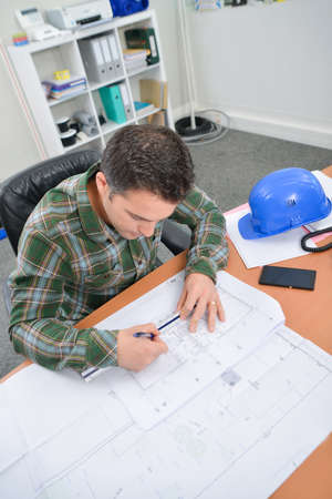 amend: Downward view of man working on scale drawings