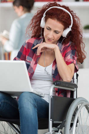 telemarketer: handicapped woman on wheelchair working from home as telemarketer