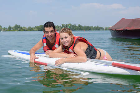 sailboard: Couple leaning over board in lake