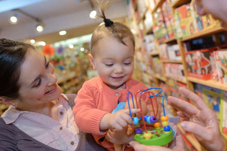 conundrum: young mother her daughter shopping at the toy store Stock Photo