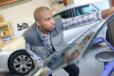 windshield: Garage worker carrying windshield