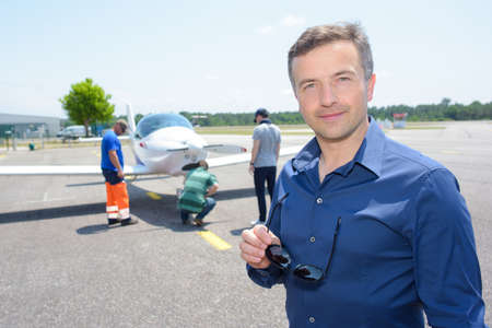 cessna: Portrait of man on runway with light aircraft