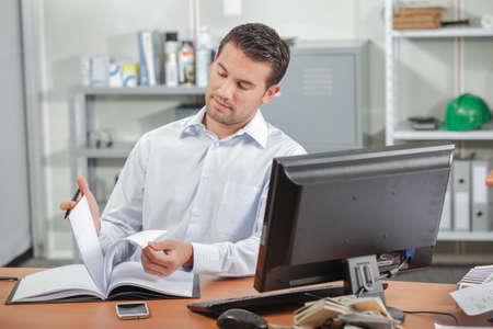 alarmed: Office worker reading at his desk