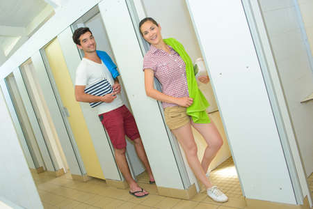 Man and woman stood in cubicle doorways Stock Photo