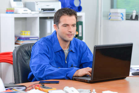 Builder using a laptop computer Stock Photo