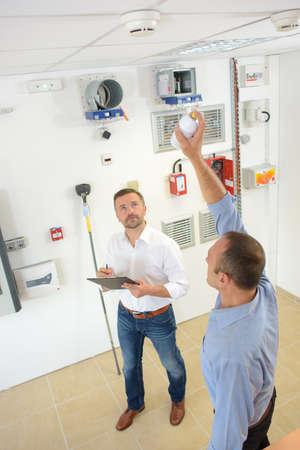 Men testing smoke detectors Banque d'images