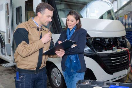 Mecánico discutiendo reparaciones de autocaravana con mujer