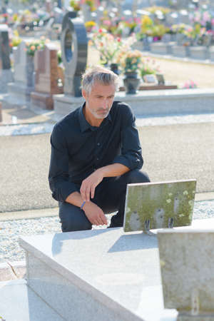 grieving: man mourning at grave